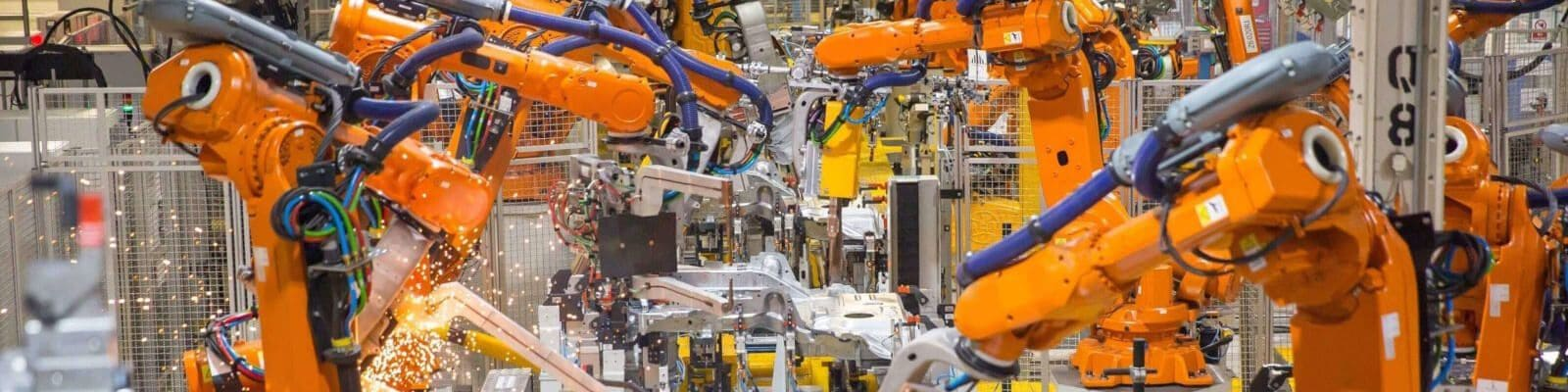 Production line with robotic arms in motion.